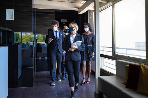 Business colleagues entering the office wearing protective face masks
